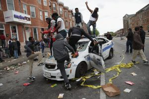 Rioters in Baltimore destroying police car.