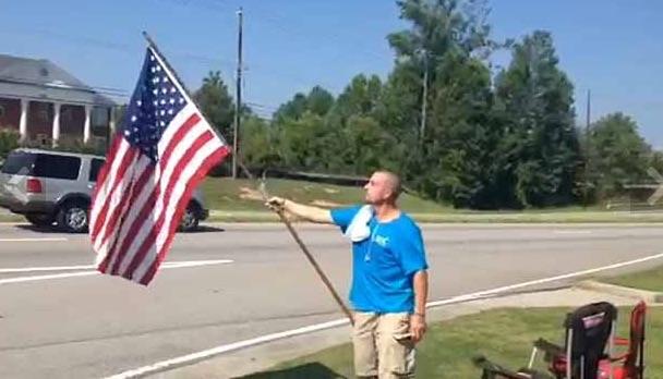 Hiram resident waving flag outside his local recruitment center. (Photo Credit: My Fox Atlanta)
