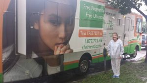 Lisa Budd, ultrasound technician, stands in front of the Thrive bus offering free ultrasounds outside of Planned Parenthood.