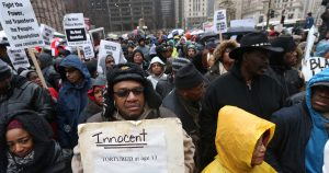 """A collection of elected officials, community activists and labor leaders listen to a prayer before a demonstration billed as a """"march for justice"""" along Michigan Avenue in Chicago on Friday, Nov. 27, 2015, in the wake of the release of video showing an officer fatally shooting Laquan McDonald. (Chris Walker/Chicago Tribune/TNS via Getty Images)"""