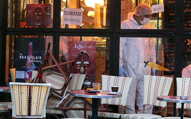 Police search for evidence inside the Comptoir Voltaire cafe, where Ibrahim Abdeslam blew himself up. (Photo: AFP PHOTO/KENZO TRIBOUILLARD)