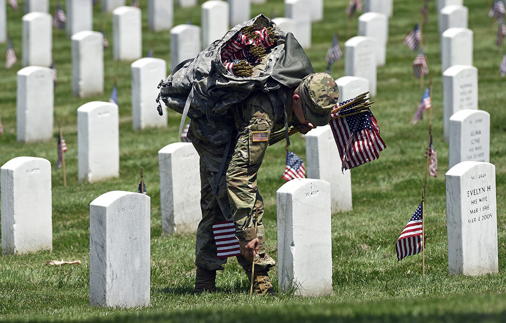 Members of the Old Guard place flags in front of every headstone at Arlington National Cemetery in Arlington, Va., Thursday, May 26, 2016. (AP Photo/Susan Walsh)
