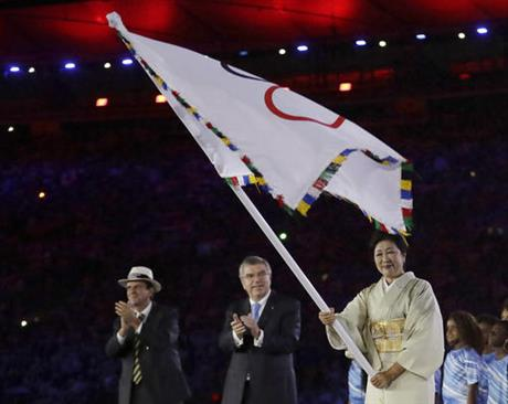 Tokyo Governor Yuriko Koike, right, waves the Olympic flag as Eduardo Paes, mayor of Rio de Janeiro, left, and IOC President Thomas Bach applaud. (photo: AP/David Goldman)