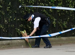 A police officer places flowers in Russell Square, Jonathan Brady/PA Wire.