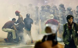 People maneuver amongst tear gas in uptown Charlotte, NC during a protest of the police shooting of Keith Scott, in Charlotte, North Carolina, U.S. September 21, 2016. REUTERS/Jason Miczek