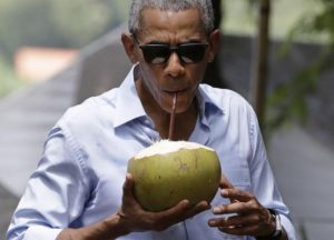 Obama drinks from a fresh coconut in Laos.