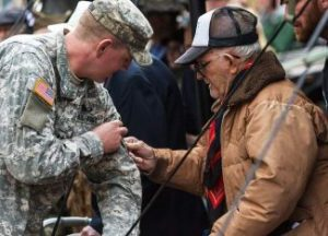 Clarence F. Dawson (Monk), veteran of the U.S. Army's 86th division company H, places a 10th Mountain patch on a 1-157th Infantry Army soldier during a re-patching ceremony Sunday at Camp Hale. Certain troops were chosen to receive their patches directly from WWII veterans like Dawson, as the first battalion, 157th Infantry became part of the third maneuver battalion of the 86th Infantry Battalion Combat Team under the 10th Mountain Division on Sunday. (photo credit - John LaConte Vail Daily)