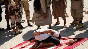 The first man is handcuffed and made to kneel on a carpet in the town square